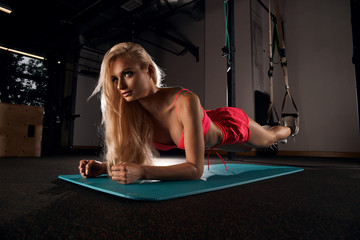 Gorgeous blonde woman with long hair, dressed in pink sports bra and shorts, performing plank with her forearms placed on green mat and toes hooked through straps. Female model demonstrating exercise.