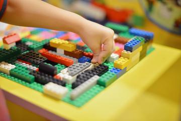 Little boy playing plastic blocks construction indoor