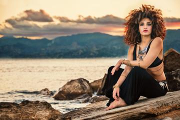 ragazza danza sugli scogli al tramonto in riva al mare