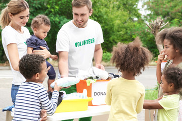 Volunteers sharing clothes and toys with poor African children outdoors