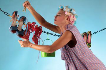 Frau mit Lockenwicklern hängt Schuhe zum Trocknen auf