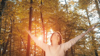 Woman enjoying beautiful autumn forest at sunset