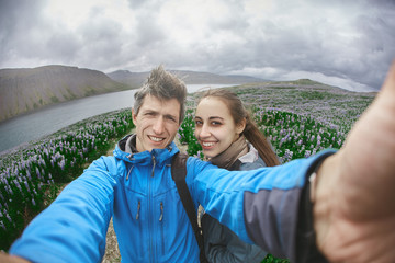Couple in warm outdoor clothing makes selfie photo on background of mountains and sea of Iceland. A field of flowering lupines in the background. Beautiful summer landscape in Iceland
