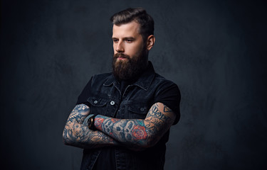 Studio portrait of bearded hipster male with tattoos on his arms.