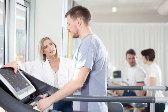 athlete on a treadmill with physiotherapist doctor