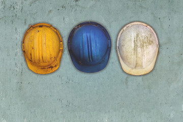 Three old and worn construction helmets