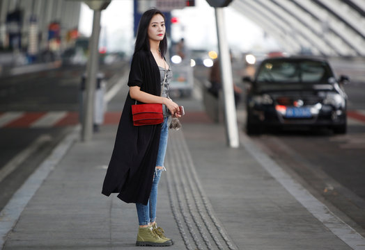 Interior designer Zheng Yue poses for a picture at the airport in Chengdu