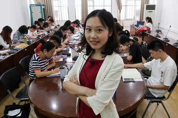 English teacher Fu Shiwei poses for pictures in her classroom in Wuhan