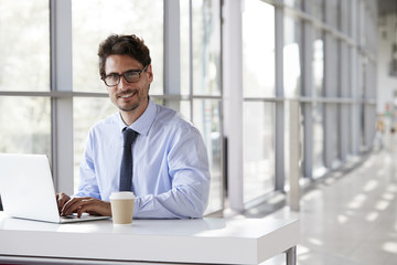 Young businessman smiling while working on his laptop