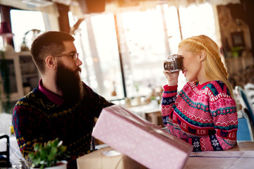 Beautiful blonde girl taking picture of her boyfriend for Christmas with presents on the table.