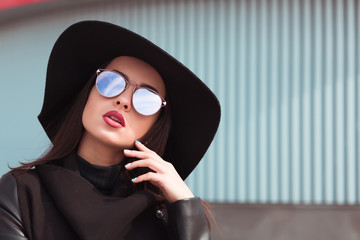 Street portrait of beautiful woman in trendy black coat and stylish hat.Female fashion concept