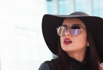 Street portrait of beautiful model in fashionable black coat and stylish hat.Female fashion concept
