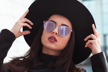 Street portrait of fashionable model in trendy sunglasses and stylish hat. Female fashion concept