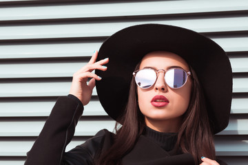Closeup portrait of young seductive model wears hat and sunglasses. Woman posing at the background of shutters in sunny day