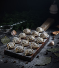 Traditional russian uncooked ravioli on black concrete background