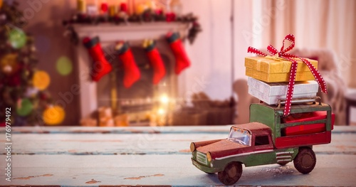 Composite image of car toy on wooden surface