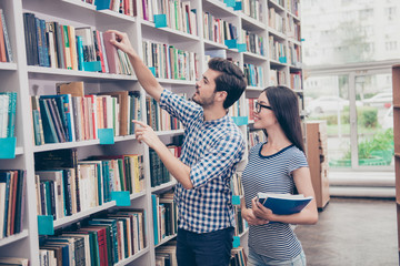 Couple of international students are in the library together after studies, smiling, dressed in comfortable casual wear, holding books, helping each other, book shelves background
