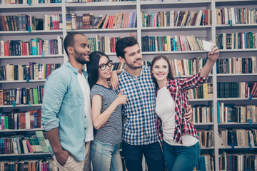 Four international students with beaming smiles are posing for selfie photo, caucasian attractive lady is doing, in school library building. Gathered, cheerful, smart and successful youth
