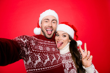 Funky, happiness, party! Cool funny playful partners bonding hug embrace in knitted traditional clothing, head wear, taking selfie with sticking tongues, making comic grimaces, fooling around