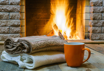 Orange  mug  for tea or coffee,  woolen things near  cozy fireplace, in country house, winter vacation, horizontal.