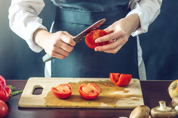 The chef in black apron cut the tomatoes. Concept of eco-friendly products for cooking