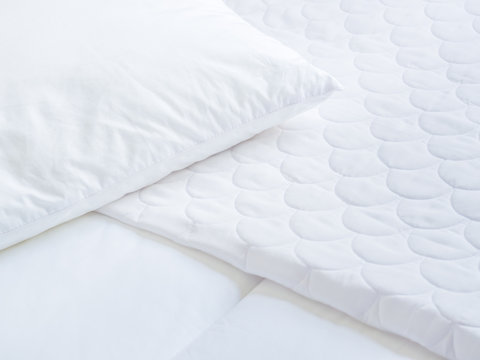 Closeup of white pillow cover sheet and topper bed.