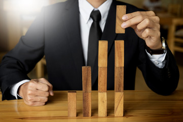 Concept growing value. hand of businessman pick up a wooden block like bar graph growth.