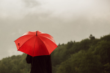 Man with red umbrella standing in the rain