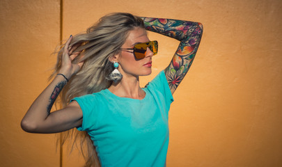 Beautiful blonde in sunglasses posing at the camera. Portrait on the background of bright orange wall. Modern hipster girl with tattoos. Closeup portrait.