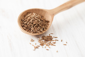 Cumin seeds in wooden spoon on white wooden table