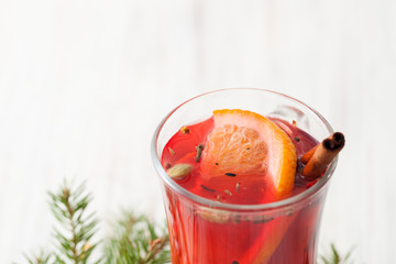 Part of a glass of mulled wine with slice of orange and cinnamon