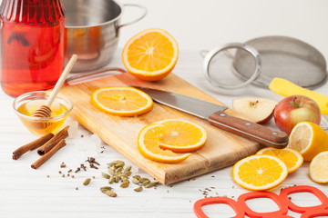 Cut the oranges and spices for mulled wine on a white table