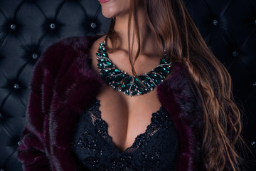 Sexy girl in an emerald necklace on a dark background