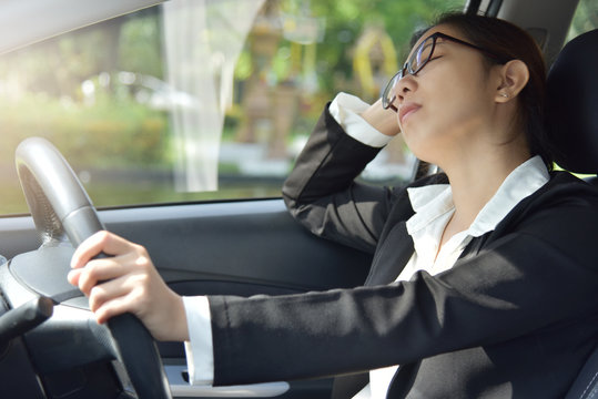 Business woman sleeping while driving a car.