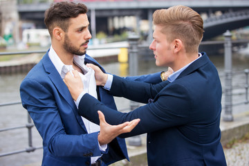 two businessmen having a fight outside