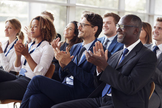 Smiling audience applauding at a business seminar