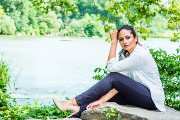 Young Beautiful East Indian American Woman traveling, relaxing at Central Park, New York, wearing white shirt, black pants, high heels, sitting on rocks by lake, looking around..