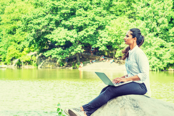 Young East Indian American Woman wearing white shirt, black pants, white sneakers, sitting on rocks by lake at Central Park, New York, typing, working on laptop computer, looking up, thinking..