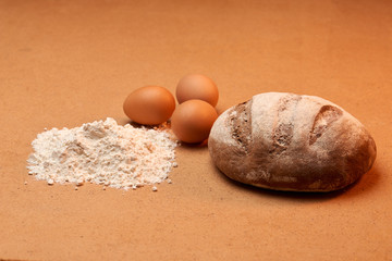 flour with three eggs and a loaf
