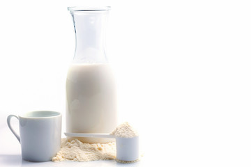 Bottle of fresh milk with powdered milk and spoon for baby on white background.