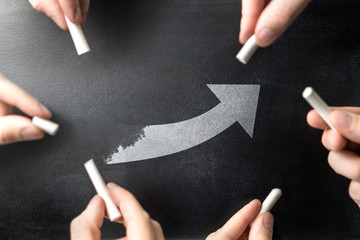 Successful teamwork, productive innovation process and development concept. Mutual goal. Working together in business or school. Team and group of people drawing arrow on same chalkboard or blackboard