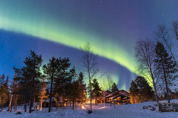 Tuinposter Noorderlicht Green Northern lights belts in a blue sky over a cottage in the lapland forest