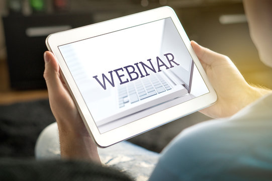 Webinar on tablet screen. Man holding smart mobile device and participating in a web seminar.