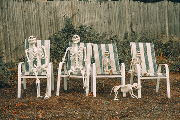 family of skeletons sits on deck chairs near the house. two skeletons of adults, two skeletons for children and a skeleton of a dog outside