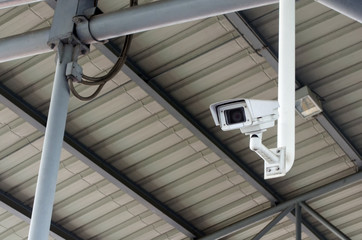 CCTV, security camera system operating under roof, surveillance security and safety technology concept