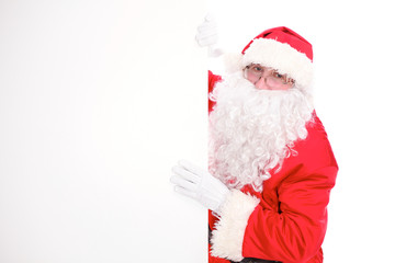 Kind Santa Claus pointing in white blank sign, isolated on white background