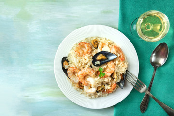 Seafood risotto plate on teal textures with copyspace