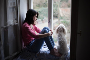 Beautiful woman and her white dog sitting on the window