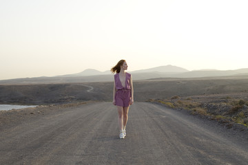 young woman walking down road in deserted landscape