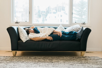 Father and son, napping on a couch